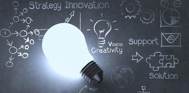 bombilla encendida con una pizarra detrás y conceptosde estrategia y negocio escritos