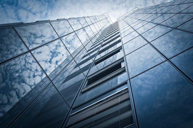 edificio rascacielos con el reflejo de las nubes y el sol en los cristales | gestión de los bufetes de abogados